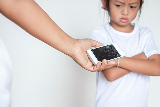 Garota ela não aceita que o celular da mãe foi quebrado. Foto Premium