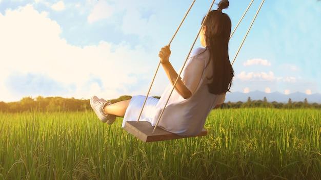 Garota em balanço na luz solar. Foto Premium