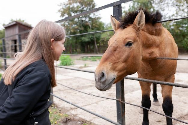 Garota em contato com um cavalo no zoológico. Foto Premium