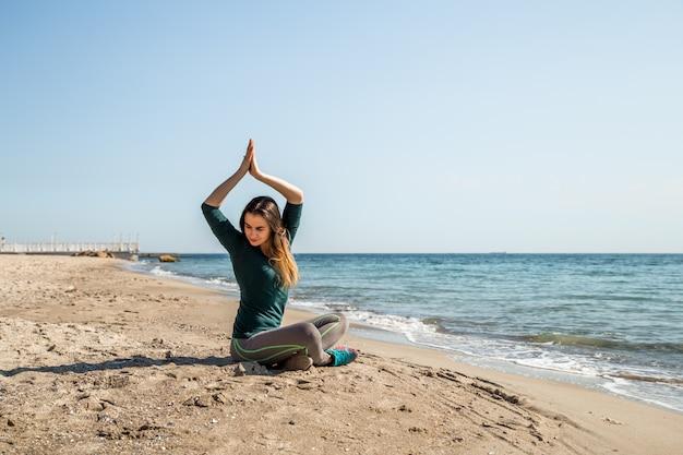 Garota em fitness sportswear à beira-mar ouvindo Foto gratuita