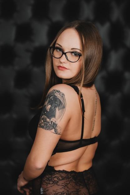 Garota em lingerie sexy preta e óculos com uma tatuagem no braço, posando em uma parede preta Foto Premium