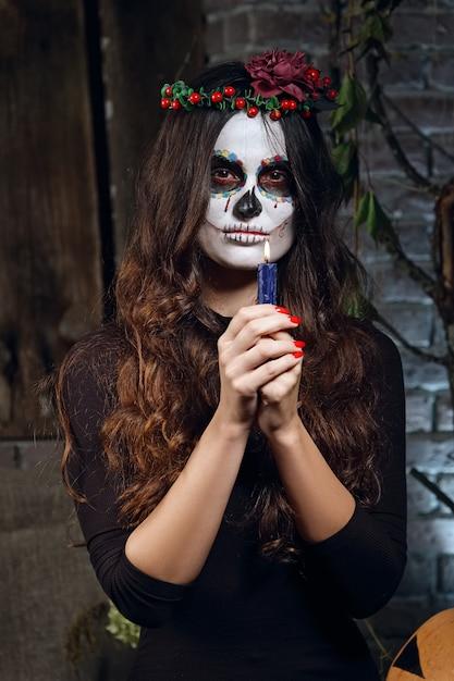 Garota em maquiagem de caveira de açúcar segurando vela nos braços dela. arte de pintura de rosto. Foto Premium