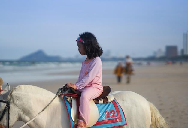 Garota em traje de banho andar a cavalo em frente à praia nas férias de verão Foto Premium