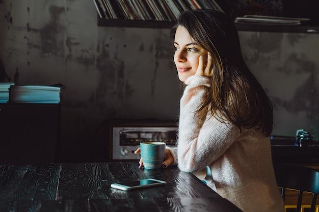 garota em um café com um smartphone Foto gratuita
