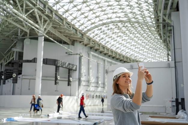 Garota em um capacete com um telefone tira fotos Foto Premium