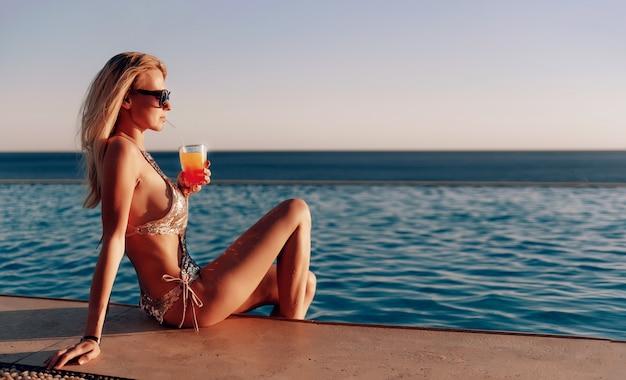 Garota em um maiô caro com um coquetel nas mãos passa as férias perto da piscina no resort Foto Premium