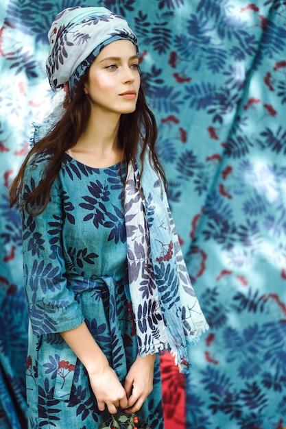 Garota em um vestido de linho. com uma coroa de flores na cabeça. Foto gratuita