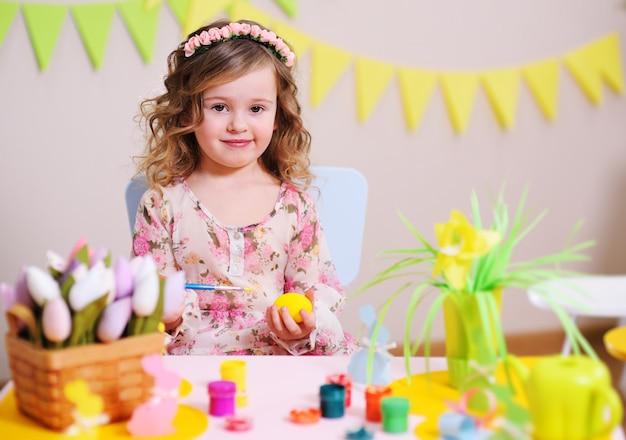 Garota em um vestido inteligente pinta um ovo sentado em uma mesa com uma decoração de páscoa Foto Premium