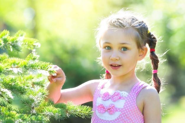 Garota em um vestido rosa na floresta. Foto Premium