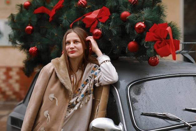 Garota em uma caminhada de inverno na cidade, neve, lá fora. rua de inverno na cidade. garota feliz caminha na cidade no dia de natal. Foto Premium