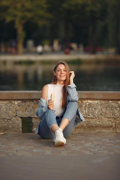 Garota em uma jaqueta jeans azul em uma cidade de verão Foto gratuita