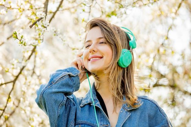 Garota em uma jaqueta jeans e fones de ouvido fica perto de uma árvore de florescência Foto Premium