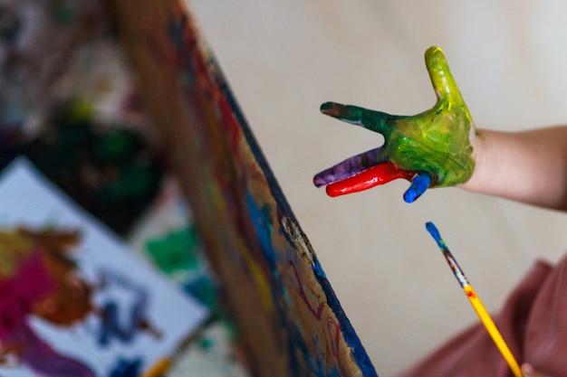 Garota engraçada criança feliz mostra as mãos sujas com tinta Foto Premium