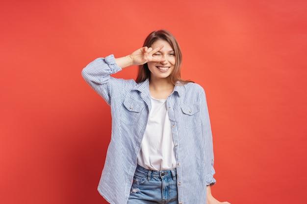 Garota engraçada e despreocupada se divertindo isolado em uma parede vermelha Foto gratuita