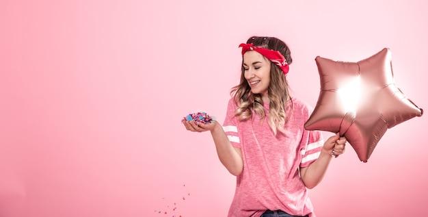 Garota engraçada em uma camiseta rosa com balões e confetes dá um sorriso e emoções em um fundo rosa Foto gratuita