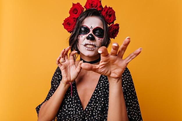Garota engraçada rosna e mostra unhas como gato. retrato da bela mexicana com maquiagem para o halloween. Foto gratuita
