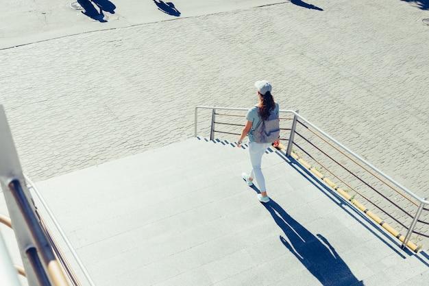 Garota esbelta em um boné e jeans andando nas escadas da cidade no verão Foto Premium