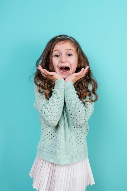 Garota espantada em pé no fundo azul Foto gratuita