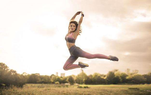 Garota esportiva pulando em um campo Foto Premium