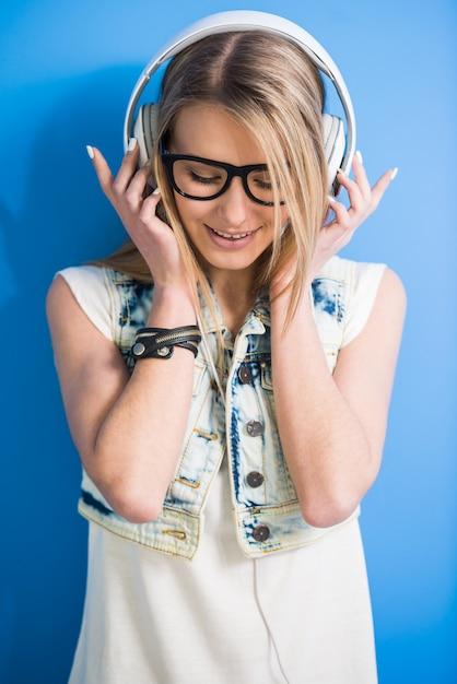 Garota está ouvindo uma música com fone de ouvido Foto Premium