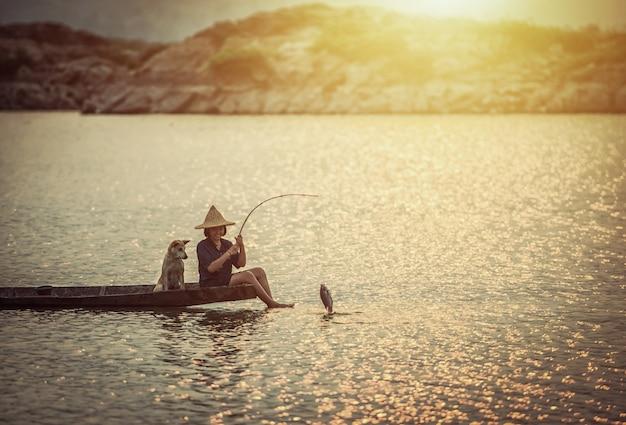 Garota está pescando no barco com seu cachorro Foto Premium