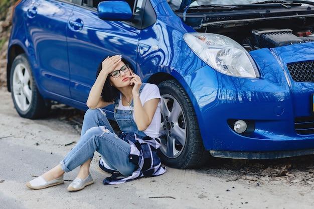 Garota está sentada ao lado de carro quebrado com um capô aberto e fala por telefone Foto Premium