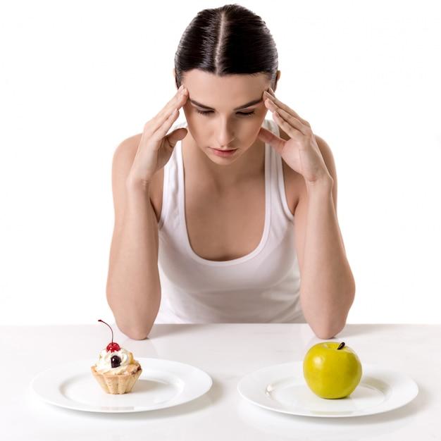 Garota está sentado e escolhendo entre um bolo e uma maçã. conceito de dieta Foto Premium
