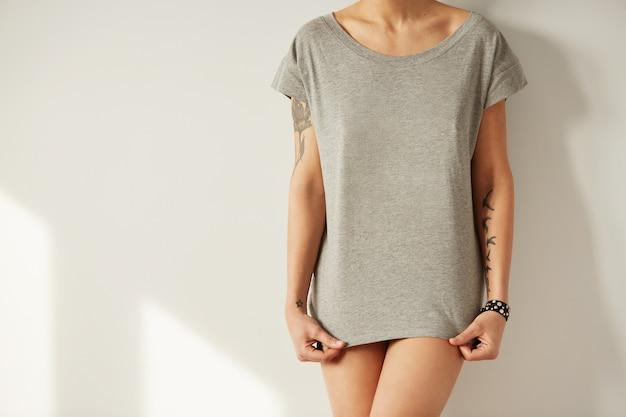Garota estilosa vestindo camiseta em branco e olhando para baixo Foto gratuita