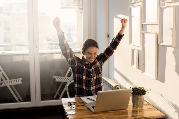 Garota eufórica em casa, olhando para a tela do computador Foto Premium