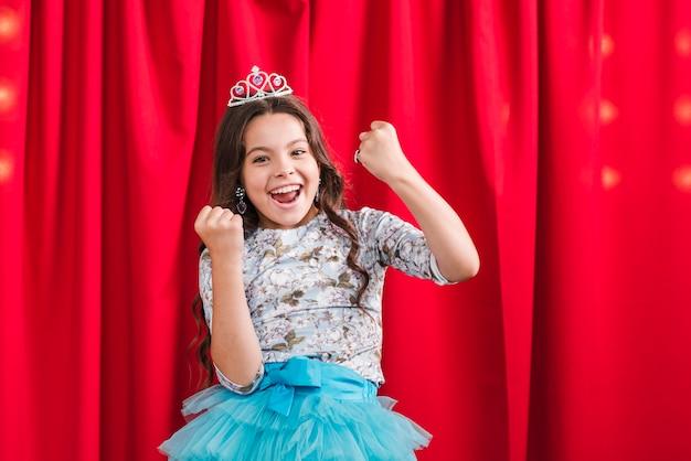 Garota excitada em pé na frente da cortina vermelha Foto gratuita