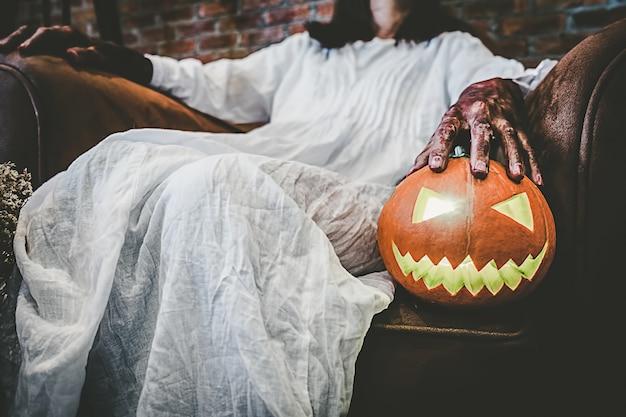 Garota fantasma no sangue com vestido branco segurando a abóbora de halloween e sentado na velha Foto Premium