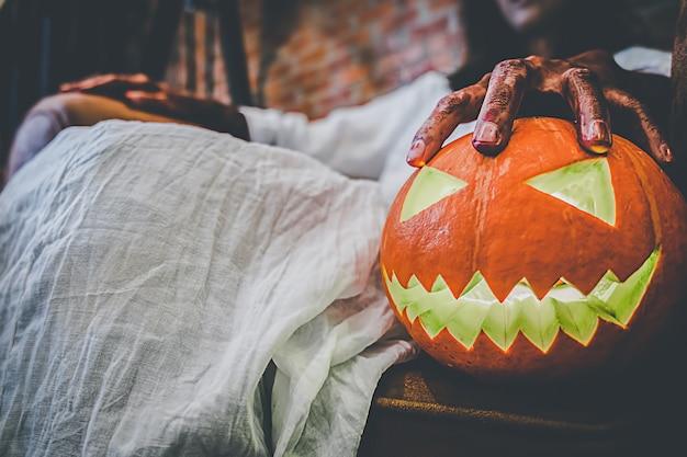 Garota fantasma no sangue com vestido branco segurando a abóbora de halloween Foto Premium