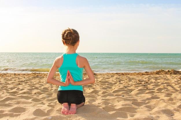 Garota fazendo exercícios de esportes na praia Foto Premium