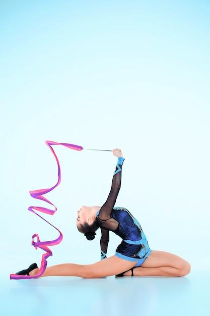 Garota fazendo ginástica dançar com fita colorida em azul Foto gratuita