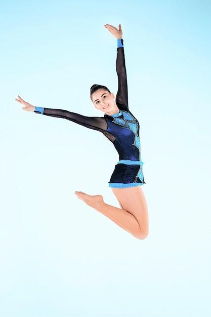 Garota fazendo ginástica dançar no azul Foto gratuita