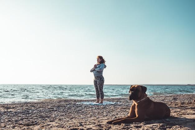 Garota fazendo ioga na praia com seu cachorro Foto Premium