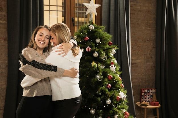 Garota feliz, abraçando a mãe para o natal Foto gratuita