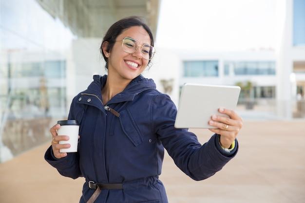 Garota feliz animada, desfrutando de café e chamada de vídeo Foto gratuita