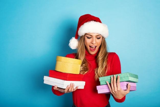 Garota feliz com chapéu de natal recebe muitos presentes. fundo ciano Foto Premium