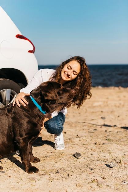 Garota feliz com seu cachorro na praia Foto gratuita