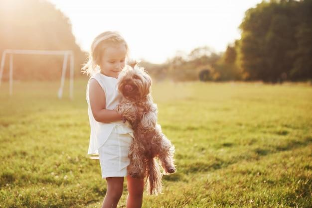 Garota feliz com seu cachorro no parque ao pôr do sol Foto gratuita