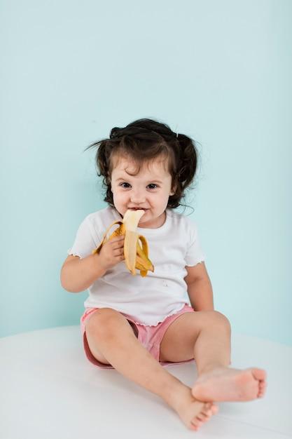 Garota feliz comendo uma banana Foto gratuita