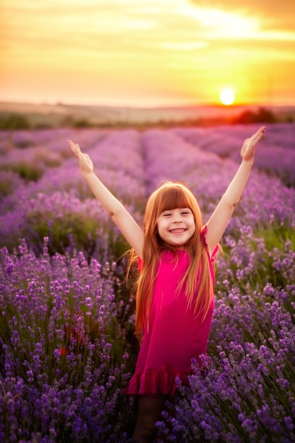 Garota feliz correndo no campo de lavanda Foto Premium