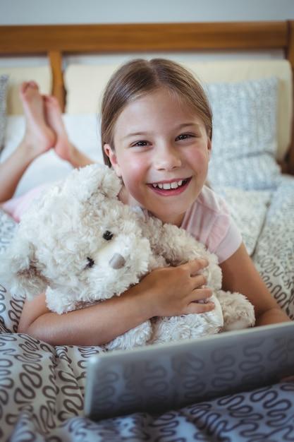 Garota feliz, deitado na cama com um ursinho de pelúcia e usando tablet digital Foto Premium