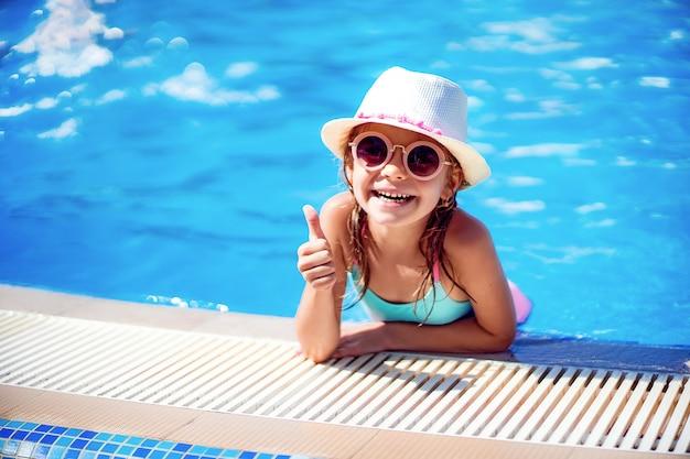 Garota feliz em óculos de sol e chapéu com unicórnio aparecer o polegar na piscina do resort de luxo nas férias de verão na ilha de praia tropical Foto Premium