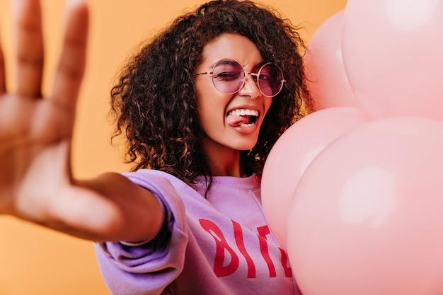 Garota feliz em óculos roxos redondos, fazendo caretas engraçadas. senhora africana refinada com cabelo escuro, posando em laranja. Foto gratuita