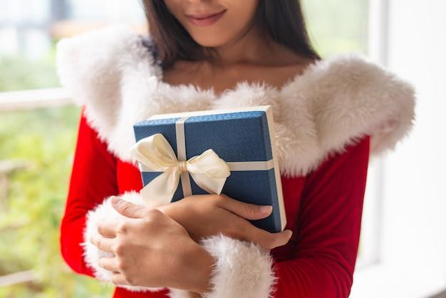 Garota feliz em traje de natal, abraçando a caixa de presente azul Foto gratuita