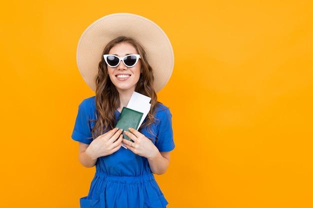 Garota feliz em um vestido azul e um chapéu de palha e óculos de sol com um passaporte e férias em amarelo com espaço de cópia Foto Premium