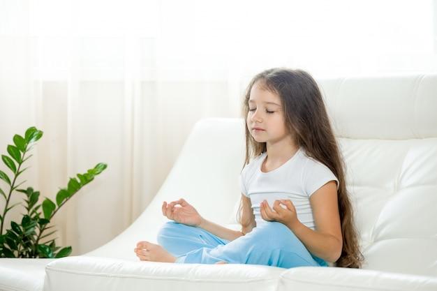 Garota feliz fazendo yoga em casa Foto gratuita