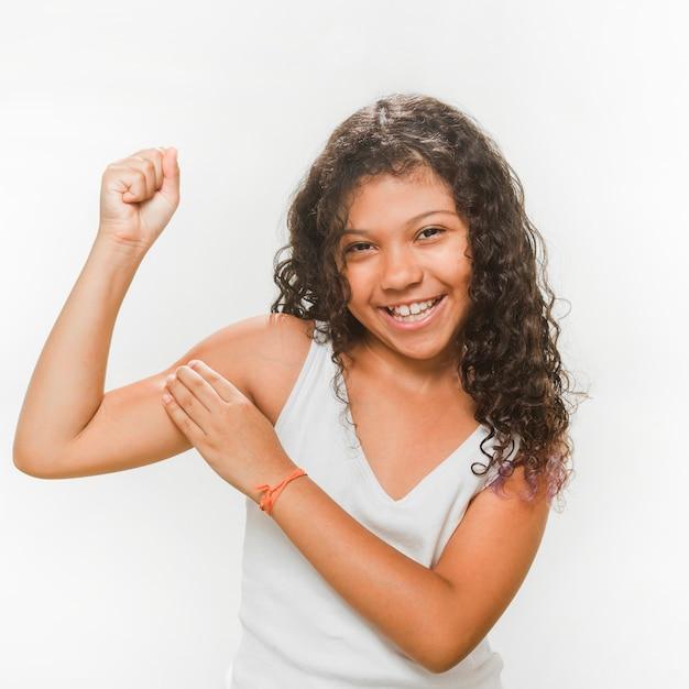 Garota feliz, flexionando seus músculos Foto gratuita